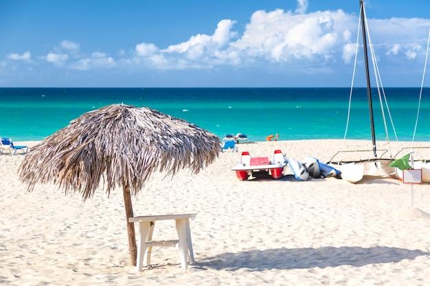 Słomiany parasol na pustej nadmorskiej plaży z żaglówką w varadero na kubie.
