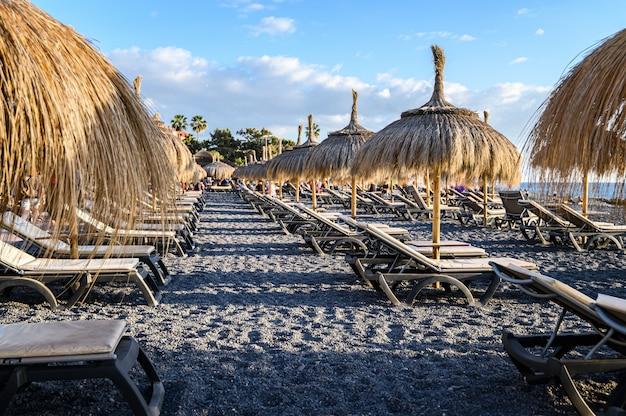 Słomiany parasol plażowy z niebieskim niebem, leżaki na czarnej wulkanicznej plaży la caletta. teneryfa, wyspy kanaryjskie, hiszpania