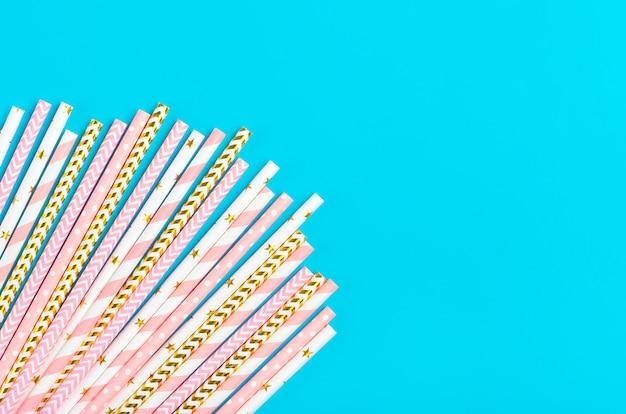 Słomki do picia na imprezę ze złotymi, białymi, pastelowymi różowymi paskami na niebieskim tle