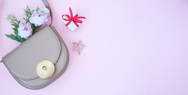 Słomkowa stylowa, nowoczesna damska torebka letnia i okulary przeciwsłoneczne oraz biały kwiat jaśminu na różowym tle.