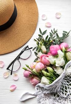 Słomkowy kapelusz i bukiet kwiatów różowej róży na białym tle. widok z góry, minimalna kompozycja w stylu płaskiej świeckiej. koncepcja wakacji letnich.