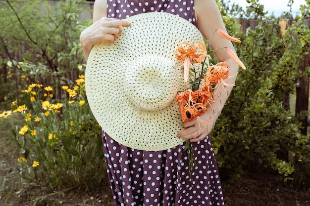Słomkowy kapelusz i bukiet lilii tygrysiej lilii lancifolium w rękach koncepcja lata i podróży