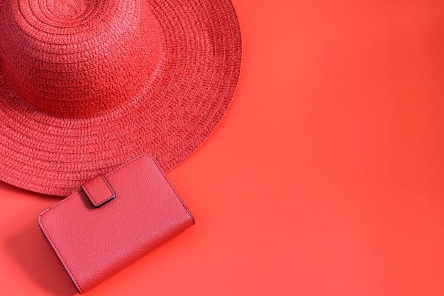 Słomkowy kapelusz i czerwony portfel na czerwonym tle