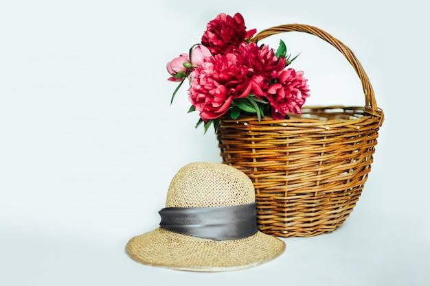 Słomkowy kapelusz i koszykowe piwonie