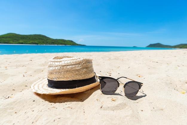 Słomkowy kapelusz i okulary przeciwsłoneczne na morzu