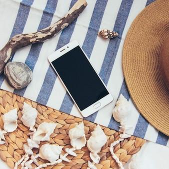 Słomkowy kapelusz i telefon komórkowy na tle plaży