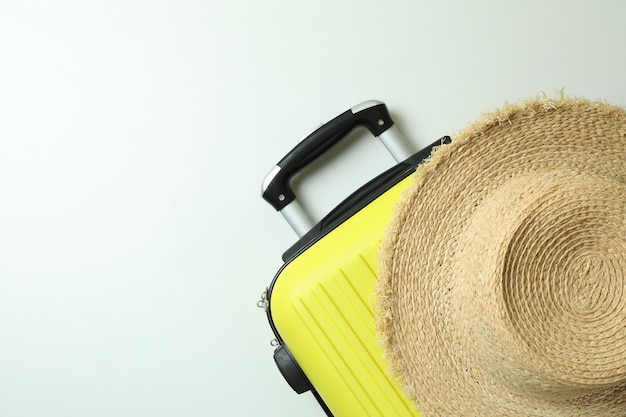 Słomkowy kapelusz i torba podróżna na białym tle