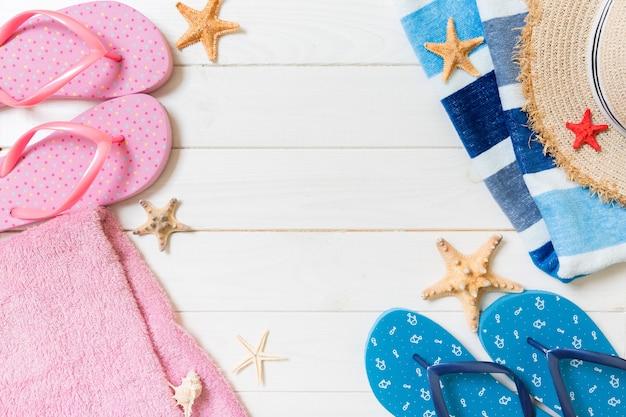 Słomkowy kapelusz, klapki, ręcznik, okulary przeciwsłoneczne i rozgwiazda na białym tle drewnianych. widok z góry koncepcja wakacji letnich z miejsca na kopię.
