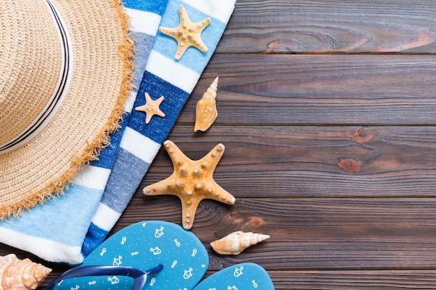 Słomkowy kapelusz, niebieskie klapki, ręcznik i rozgwiazda