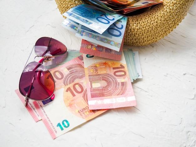 Słomkowy kapelusz, pieniądze, karty bankowe, odblaski okularów