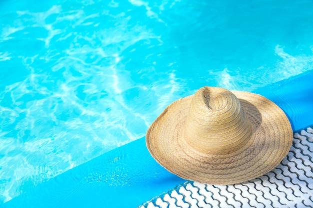 Słomkowy kapelusz przy powierzchni niebieskiego przezroczystego basenu z wolną przestrzenią.