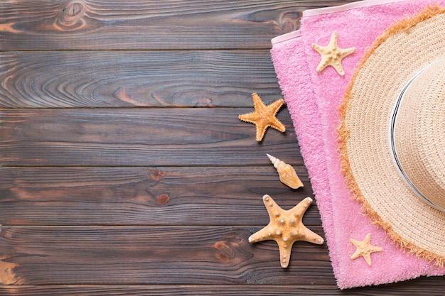 Słomkowy kapelusz, różowy ręcznik i rozgwiazda na ciemnym drewnianym tle. widok z góry koncepcja wakacji letnich z miejsca na kopię.