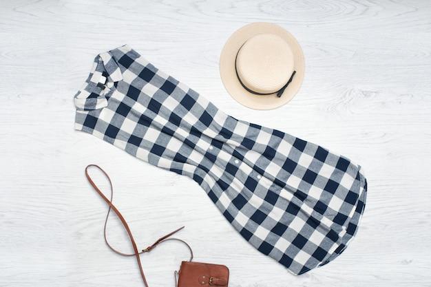 Słomkowy kapelusz, sukienka w kratkę, torebka