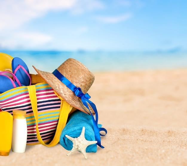Słomkowy kapelusz, torba, klapki na tropikalnej plaży