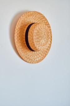 Słomkowy kapelusz wisi na haczyku.