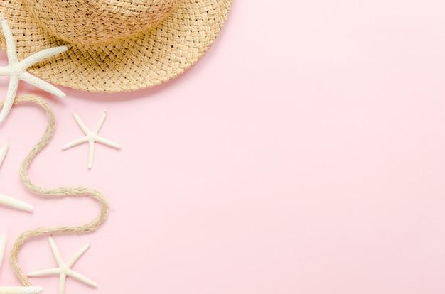 Słomkowy kapelusz z gwiazdami morza na stole