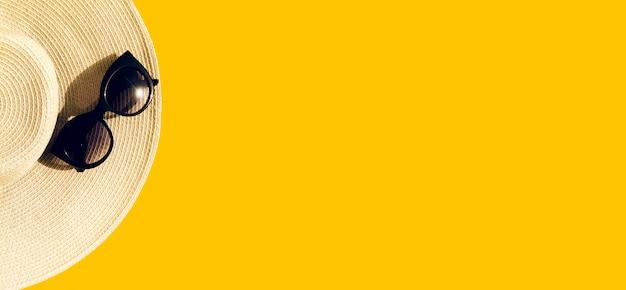 Słomkowy kapelusz z okularami przeciwsłonecznymi na kolorze żółtym