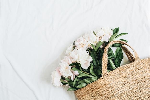 Słomkowy worek z białymi kwiatami piwonii na białej powierzchni