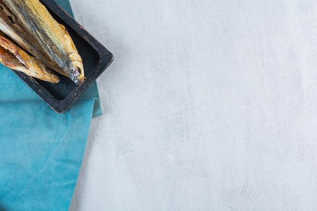 Słona suszona ryba na białym tle na drewnianej desce
