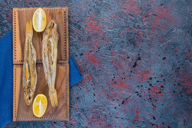Słona suszona ryba z plasterkiem cytryny na drewnianej desce