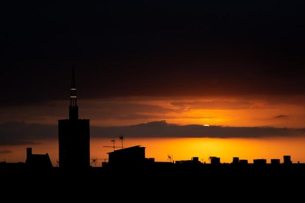 Słońce chowa się za chmurami o zachodzie słońca, widok na dach starej wieży kościoła.