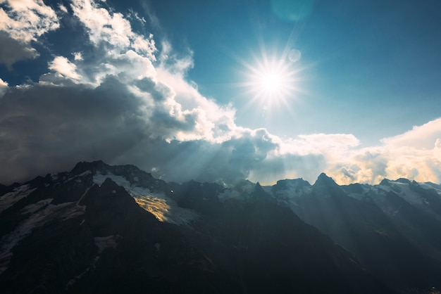 Słońce jasno świeci nad pochmurnymi, zamarzniętymi szczytami gór. promienie słoneczne świecą na górach kaukazu. ośnieżone góry pod słońcem. skopiuj miejsce
