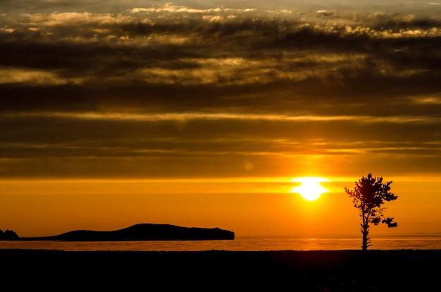 Słońce nad jeziorem, górą i drzewem o zachodzie słońca w świetle kontrastowym z chmurami