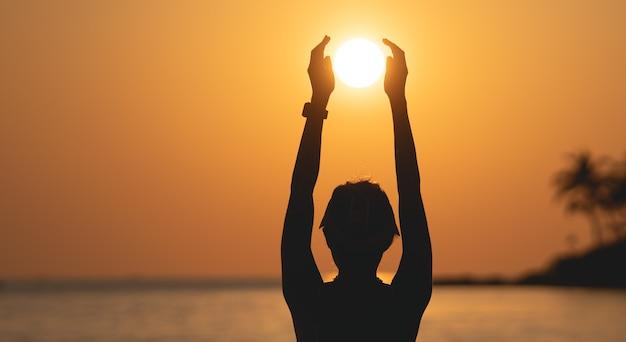 Słońce nad morzem na pomarańczowym niebie. kobieta stojąc na plaży trzymając słońce w dłoniach.