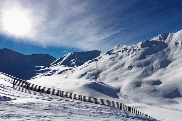 Słońce nad zimowymi górami pokrytymi śniegiem. zimny, słoneczny zimowy dzień w austriackich alpach