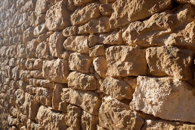 Słońce oświetla naturalne kamienne ściany zewnętrzne domów małego opuszczonego wiejskiego miasteczka.