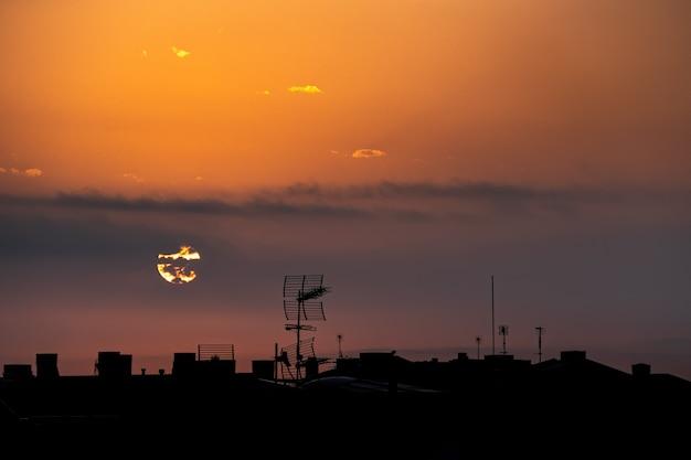Słońce pojawia się zza chmur, nad miastem, widok z góry na dach.