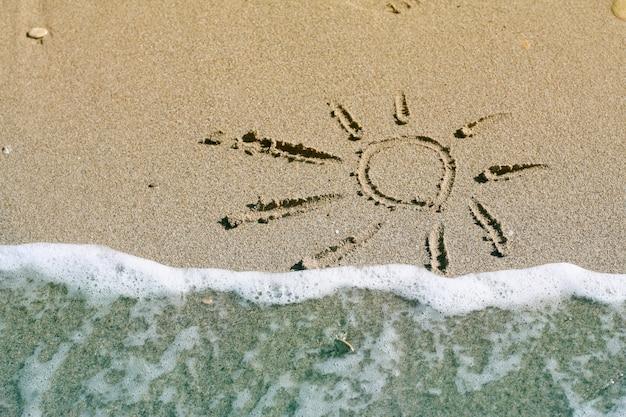 Słońce rysunek na piasku i morzu