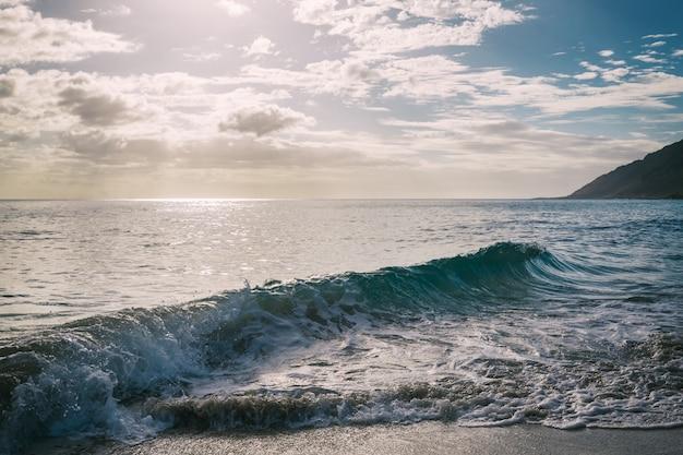 Słońce świeciło przez chmury na piaszczystej plaży z falami