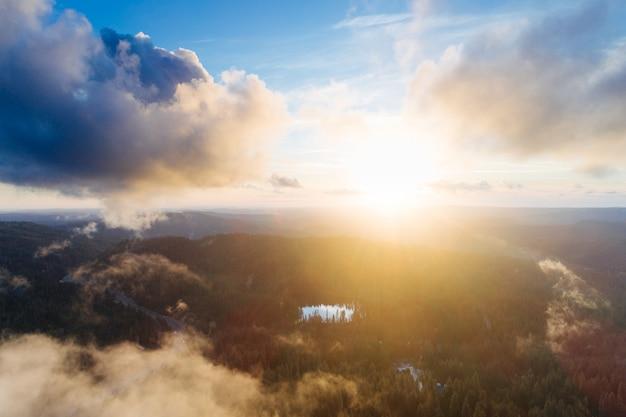 Słońce wschodzące nad formacją skalną pokrytą zielenią