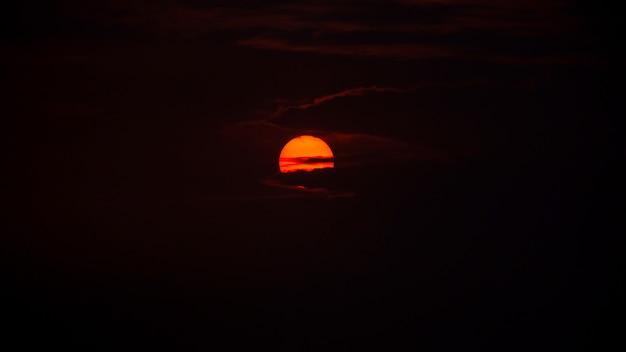 Słońce wschodzi za chmurami wczesnym rankiem, zdjęcie ma trochę hałasu i ziarna.