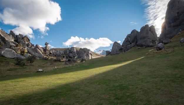 Słońce zachodzące za skałami o niezwykłych kształtach i rzucające promienie światła wzgórze zamkowe nowa zelandia