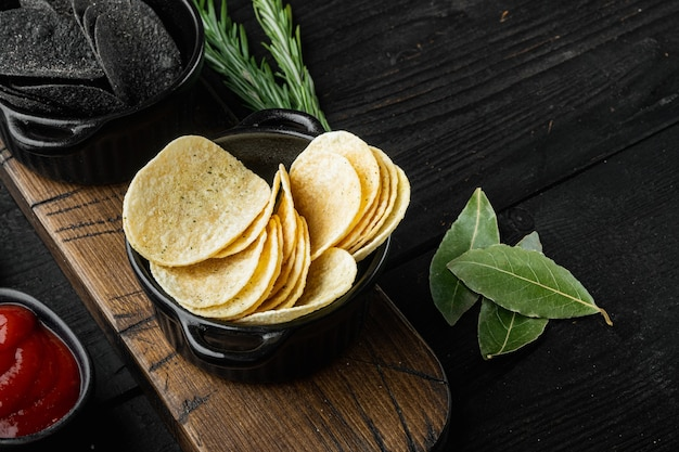 Słone chipsy ziemniaczane przekąska na czarnym tle drewniane