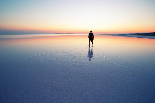 Słone jezioro tuz z mężczyzną opuszczającym o zachodzie słońca