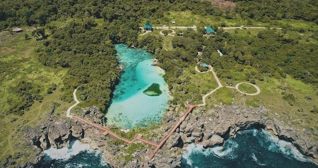 """Słone jezioro w zielonym tropikalnym krajobrazie ptaka. letnia sceneria przyrody """"nikt nie"""" weekuri, wyspa sumba, indonezja, azja. jasna laguna z zielenią lasów tropikalnych na wybrzeżu oceanu roch"""