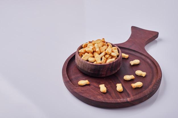 Słone krakersy w drewnianym kubku na białym tle na szarym tle