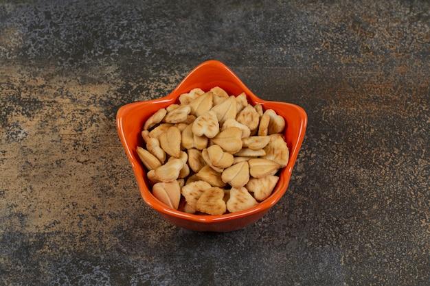 Słone krakersy w kształcie serca w misce pomarańczowy.