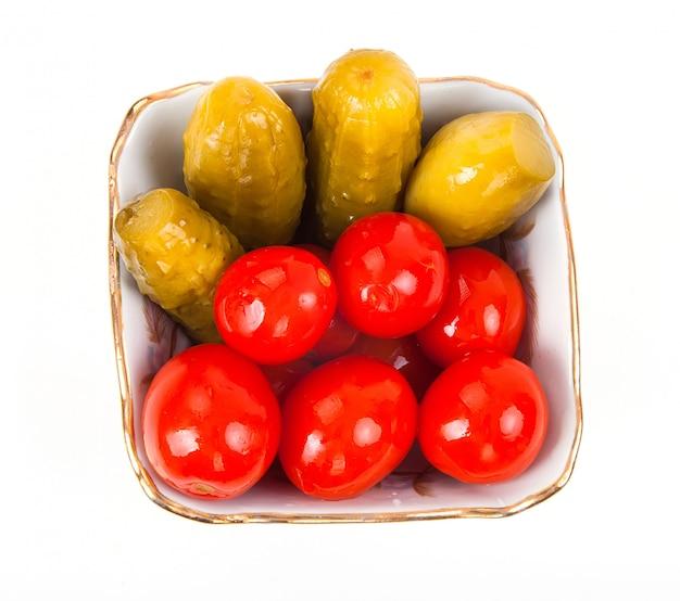 Słone marynowane pomidory i ogórki w talerzu