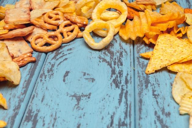 Słone przekąski. precle, frytki, krakersy na drewniane tła. niezdrowe produkty