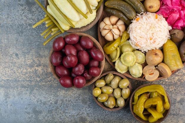 Słone warzywa w drewnianych miskach na marmurowym tle. zdjęcie wysokiej jakości