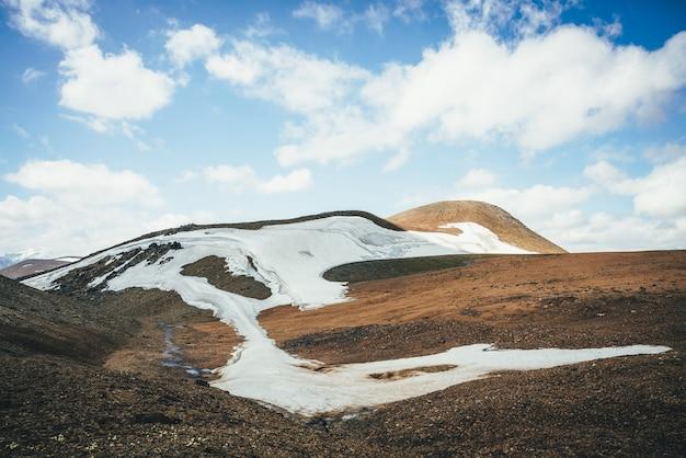 Słoneczna górska ulga pustyni z lodowcem w słońcu pod błękitnym pochmurnym niebem. malowniczy krajobraz wyżyny z małym lodowcem wysoko w górach na wzgórzach. minimalistyczna górska sceneria górskiej pustyni.