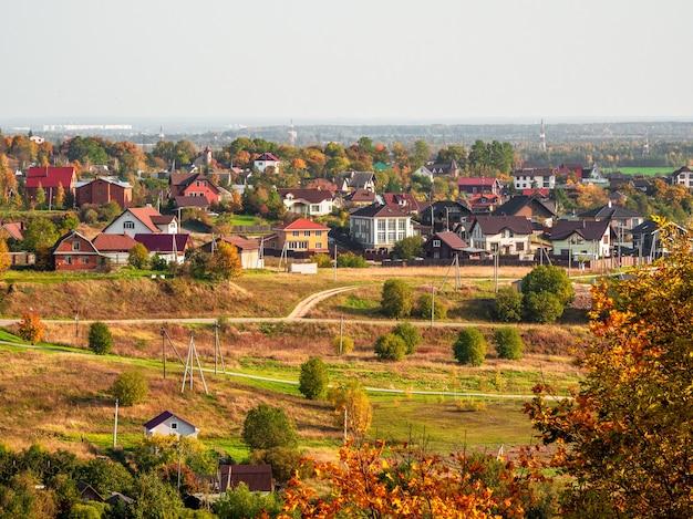 Słoneczna jesień wiejski krajobraz z domami w oddali. rosja.