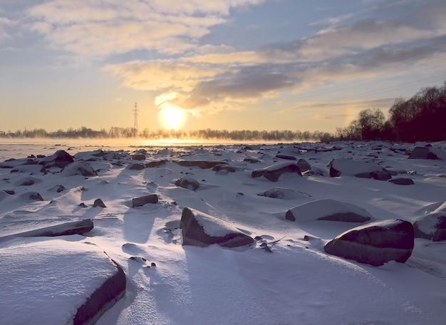 Słoneczna kula o zachodzie słońca kamienne brzegi ob pokryte są śniegiem złoto-błękitne niebo