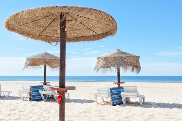 Słoneczna plaża w portugalii z drewnianymi parasolami w pobliżu morza. lato.