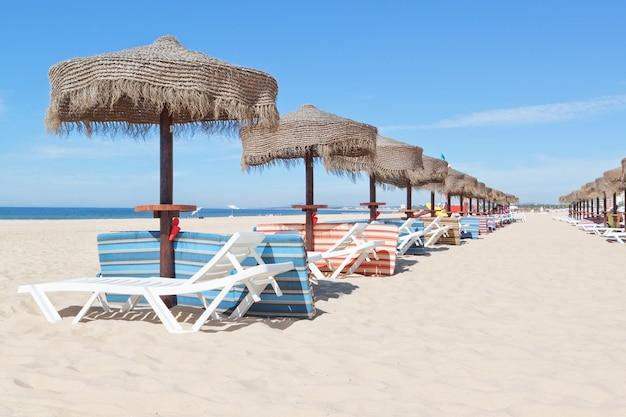 Słoneczna plaża w portugalii z linią parasoli w pobliżu morza. lato.