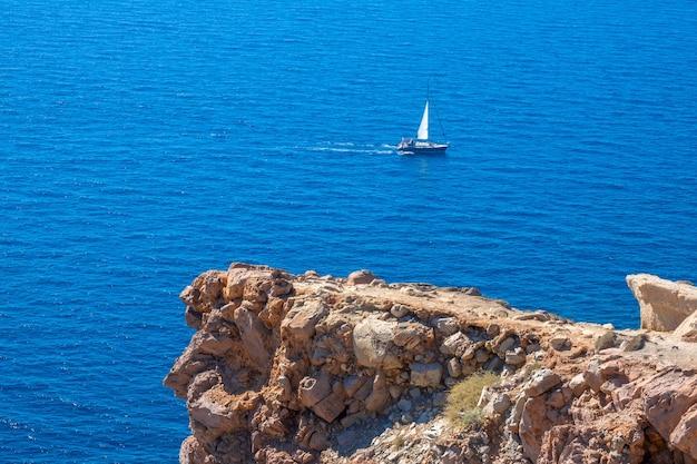 Słoneczna pogoda na skalistym brzegu. wapienny klif. samotny jacht żaglowy na błękitnym morzu
